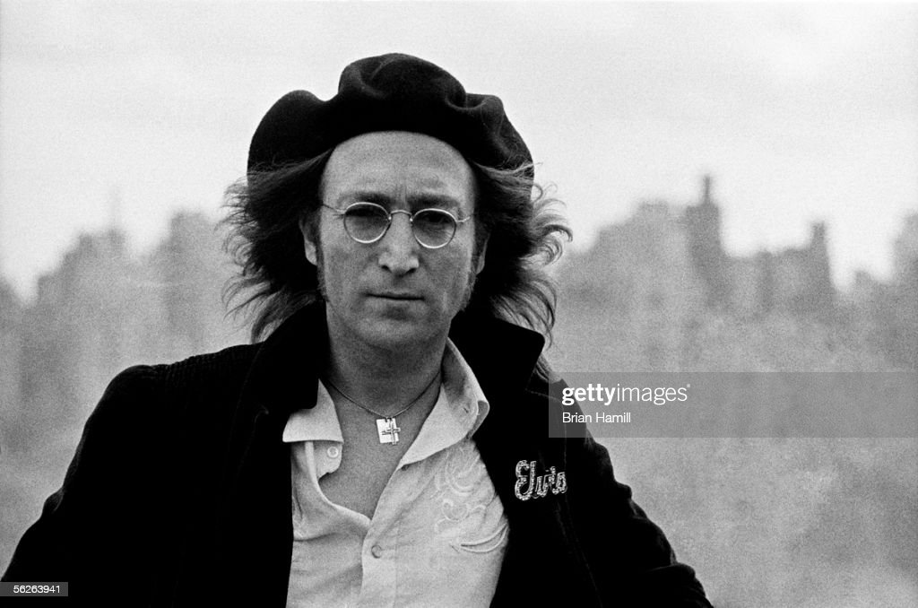 British-born singer and songwriter John Lennon (1940 - 1980) in front of an unfocused cityscape on the roof of his apartment building, the Dakota, New York, New York, February 25th, 1975. Lennon, his hair swept back from the wind, wears a beret and coat with an attached Elvis pin.