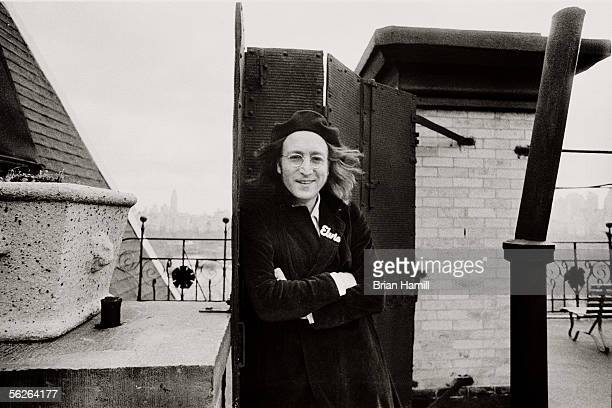 Britishborn singer and songwriter John Lennon leans against a gate with his arms crossed on the roof of his apartment building the Dakota New York...