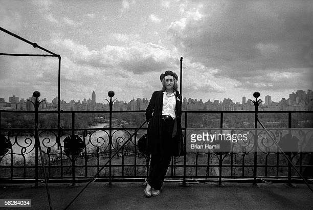 Britishborn singer and songwriter John Lennon leans on a railing which overlooks Central Park and the Manhattan cityscape on the roof of his...