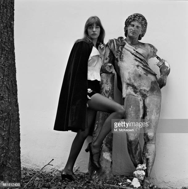 BritishFrench actress Jane Birkin wearing velvet shorts by Vicky Tiel leans on a stone statue UK 30th January 1971