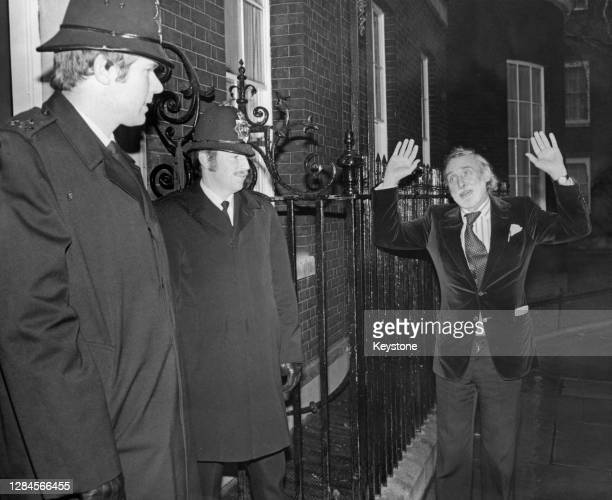 British-Irish comedian, writer and actor Spike Milligan puts his hands up as he approaches two police officers when delivering a petition, from joint...