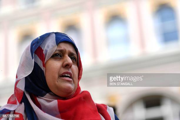 A BritishPakistani woman wearing a Union flag themed headscarf pays her respects near the floral tributes left in St Ann's Square in Manchester...