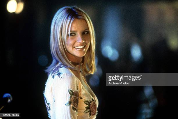 Britney Spears smiling as she looks back in a scene from the film 'Crossroads' 2002