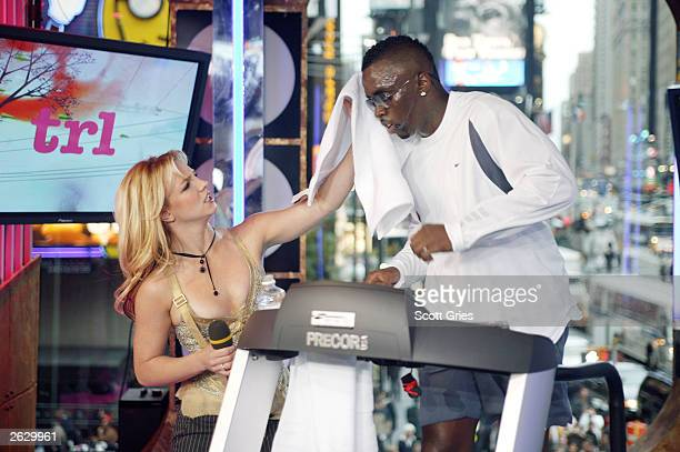 Britney Spears wipes the sweat from P. Diddy's forehead on stage during MTV's Total Request Live at the MTV Times Square Studios October 22, 2003 in...