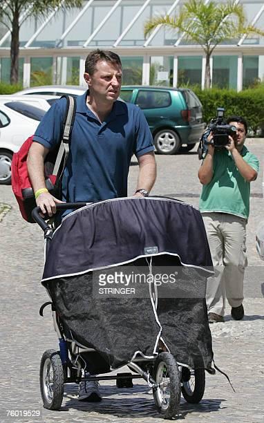 Briton Gerry McCann father of missing fouryearold Madeleine McCann pushes a stroller with his twin children aboard in Praia da Luz 08 August 2007 DNA...