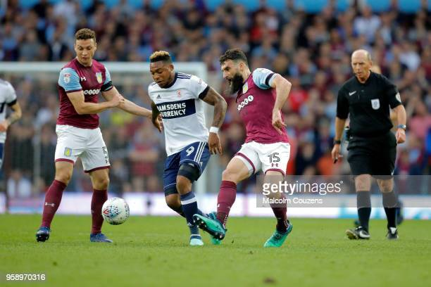 Britt Assombalonga of Middlesbrough is challenged by James Chester and Mile Jedinak of Aston Villa during the Sky Bet Championship Play Off Semi...