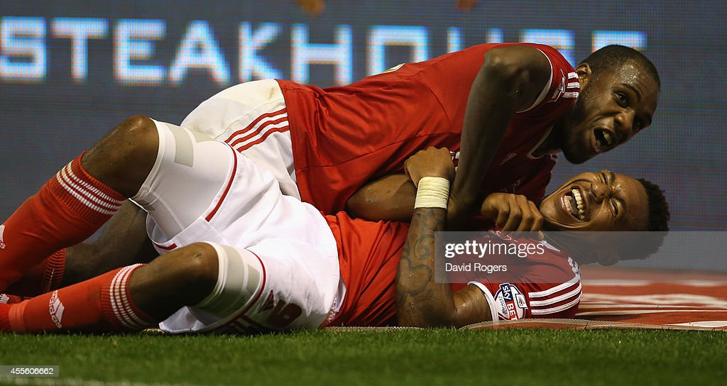 Britt Assombalonga of Nottingham Forest (bottom) celebrates with team mate Michail Antonio after scoring their fourth goal and his hat trick during the Sky Bet Championship match between Nottingham Forest and Fulham at the City Ground on September 17, 2014 in Nottingham, England.