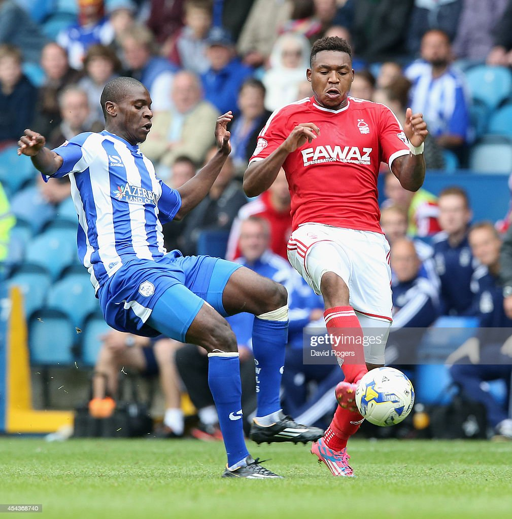Britt Assombalonga of Nottingham Forest (R) is challenged by Jeremy Helan during the Sky Bet Championship match between Sheffield Wednesday and Nottingham Forest at Hillsborough Stadium on August 30, 2014 in Sheffield, England.