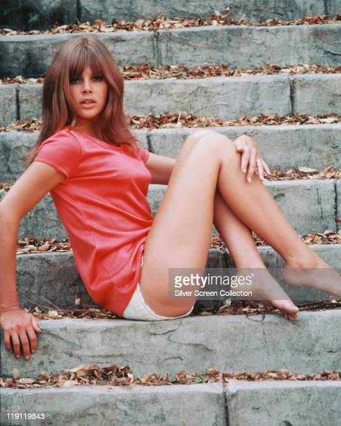 Britt Ekland, Swedish actress, wearing a pink t-shirt and sitting on a flight of stone steps, circa 1965.
