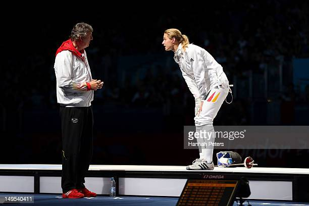 Britta Heidemann of Germany argues with her coach Manfred Kaspar after an issue with an expired clock was addressed in her bout against A Lam Shin of...