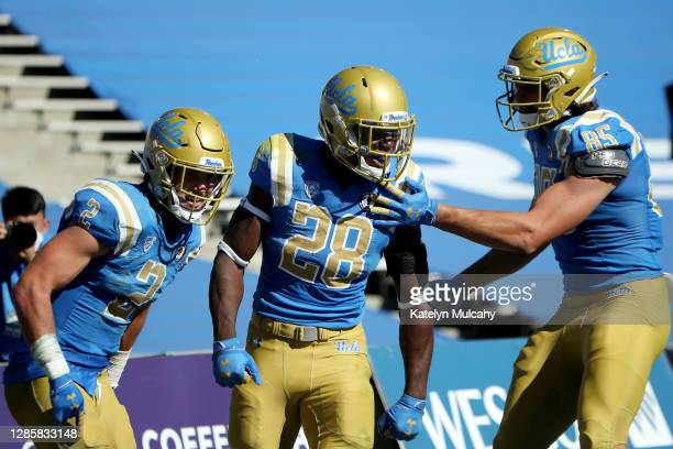 Brittain Brown of the UCLA Bruins celebrates a touchdown against the California Golden Bears with Kyle Philips and Greg Dulcich of the UCLA Bruins...
