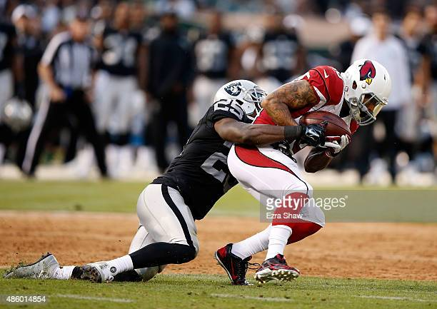 Brittan Golden of the Arizona Cardinals is tackled by D.J. Hayden of the Oakland Raiders at O.co Coliseum on August 30, 2015 in Oakland, California.