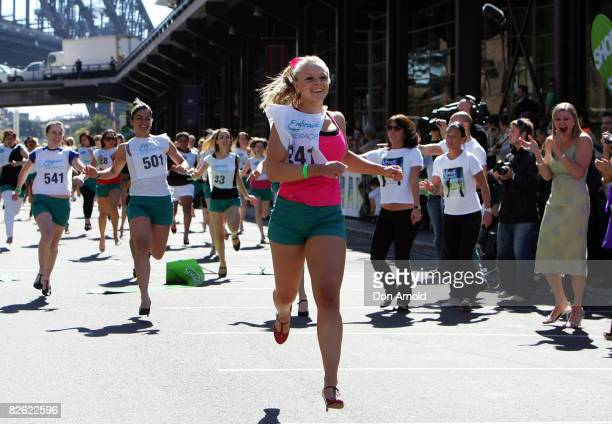Brittaney McGlone , cheered on by Melinda Gainsford-Taylor, wins a 80 metre world record attempt stiletto race at the Overseas Passenger Terminal on...