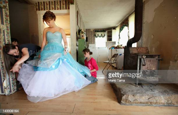 Brittany Brewer fixes her gown as she prepares for the Owsley County High School prom next to a wood stove in the home where she lives with her...