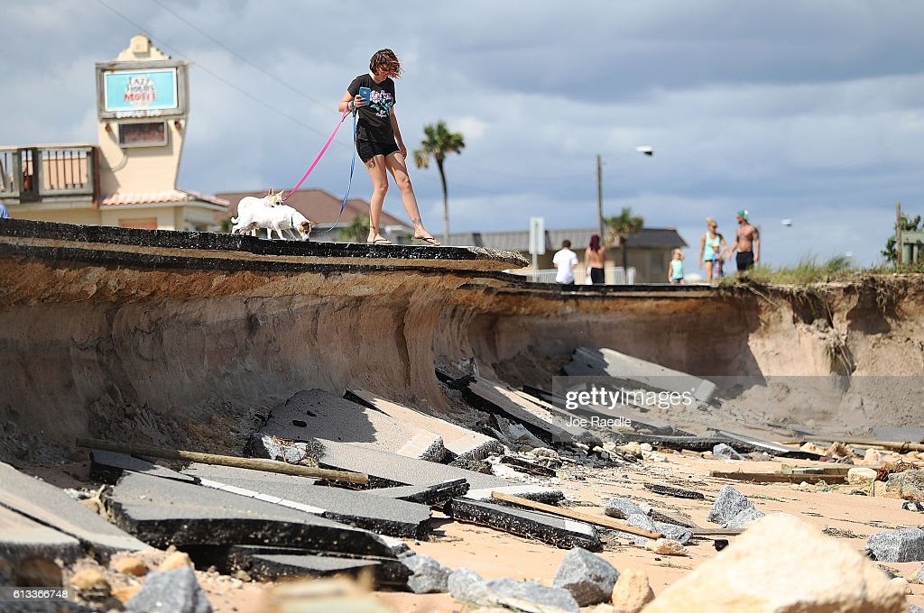 Brittany Durochar along part of A1A after ocean waters stirred up by Hurricane Matthew washed away parts of the ocean front road on October 8, 2016 in Flagler Beach, Florida. Across the Southeast, over 1.4 million people have lost power due to Hurricane Matthew which was downgraded to a category 1 hurricane on Saturday morning.