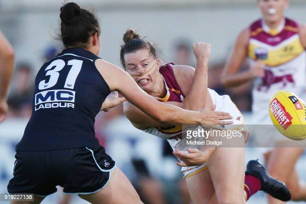 Brittany Gibson of the Lions handballs away from Danielle Hardiman of the Blues during the round three AFLW match between the Carlton Blues and the...