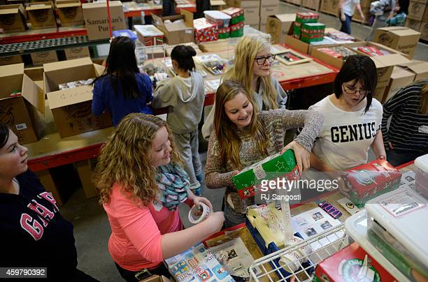 Brittany Hawkins center tapes a shoebox closed as volunteers gather in Aurora to pack shoeboxes full of Christmas gifts for children December 01 2014...