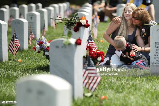 Brittany Jacobs of Hertford North Carolina and her son Christian Jacobs are embraced by a friend while sitting next to the grave of Brittany's...