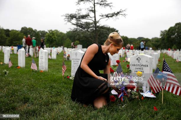Brittany Jacobs places a flower at the headstone of her husband Marine Sgt Christopher Jacobs at Arlington National Cemetery on Memorial Day May 27...