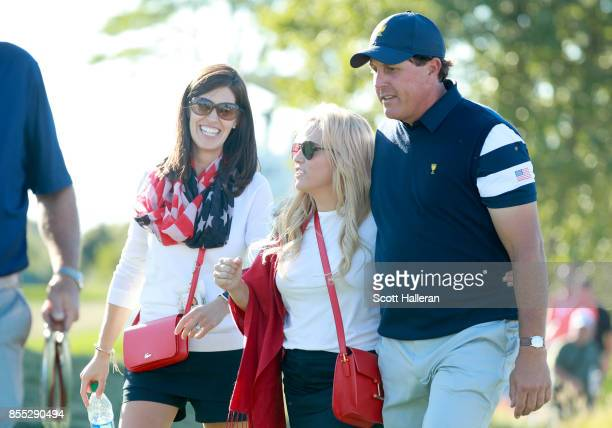 Brittany Kisner wife of Kevin Kisner walks with Phil Mickelson of the US Team and his wife Amy during the Thursday foursomes matches of the first...