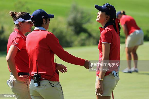 Brittany Lang assistant coach Laura Diaz and Michelle Wie of the USA talk during a practice round for the 2013 Solheim Cup on August 14 2013 at the...