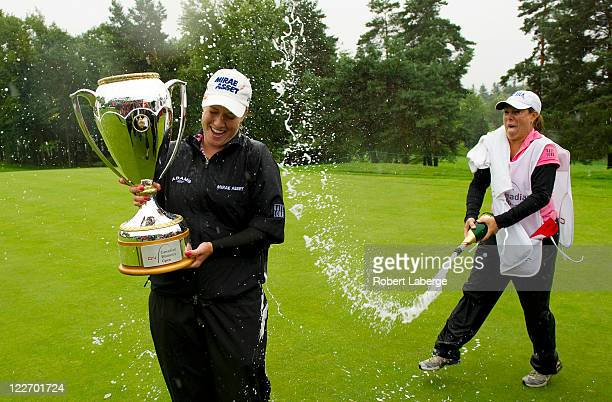 Brittany Lincicome gets sprayed with champagne by her caddie A J Eathorne after winning the CN Canadian Women's Open at the Hillsdale Golf and...