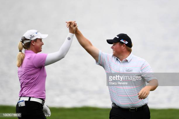 Brittany Lincicome is congratulated by Conrad Shindler after holing out for eagle in the 17th fairway during a continuation of the second round of...