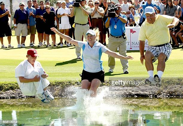 Brittany Lincicome jumps in the water surrounding the 18th green after winning with an eagle on the final hole with caddie Tara Bateman and father...
