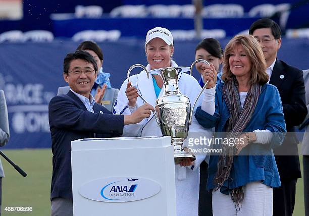 Brittany Lincicome of the USA is presented with the ANA Inspiration Dinah Shore Trophy by Mr Shinya Katanozaka the President and CEO of ANA Holdings...