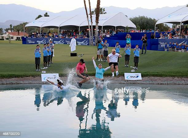 Brittany Lincicome of the USA leads the traditional cahmpions jump into 'Poppy's Pond' with her caddie Missy Pederson her fiancee Dewald Gouws and...