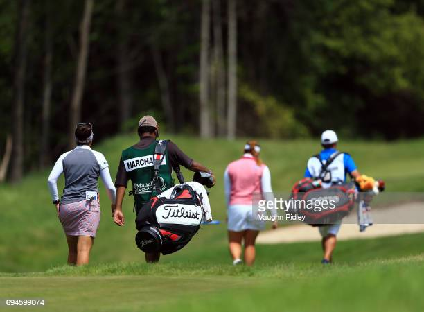 Brittany Marchand of Canada and Ariya Jutanugarn of Thailand along with their caddies walk down the 17th fairway during the third round of the...