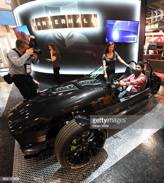 Brittany Murata of the Vanderhall Motor Works shows a Vanderhall Edison2 threewheeled autocycle to Balmeet Singh of California during CES 2018 at the...