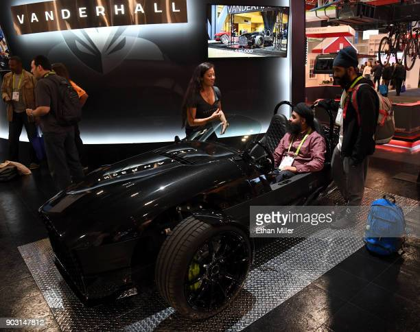 Brittany Murata of the Vanderhall Motor Works shows a Vanderhall Edison2 threewheeled autocycle to Balmeet Singh and Tanishq Saluja of California...