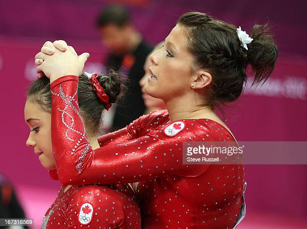 Brittany Rogers hugs Victoria Moors as they watch Elsabeth Black compete on the beam as Canada earns a fifth place finish their best all time in the...