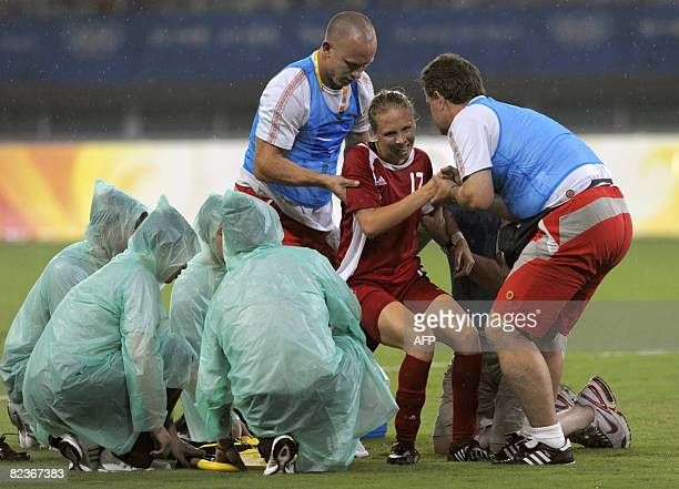 Brittany Timko of Canada is helped to stand up by a team staff as she leaves the field after an injury during the 2008 Beijing Olympic Games women's...