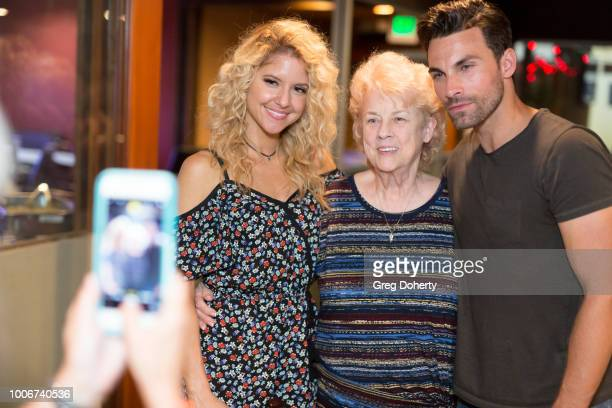 Brittany Underwood and Erik Fellows pose for a picture with a fan as they attend The Bay Cast Host Fan Appreciation Event on July 27 2018 in Glendale...