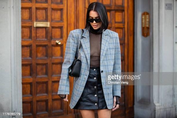 Brittany Xavier is seen weairng black mini skirt, checkered blazer, sheer top outside the Ferragamo show during Milan Fashion Week Spring/Summer 2020...