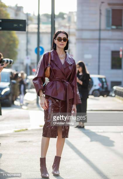 Brittany Xavier is seen wearing belted bordeaux jacket, vinyl skirt with slit, brown bag outside the Tod's show during Milan Fashion Week...
