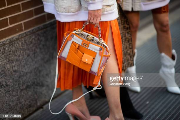 Brittany Xavier is seen wearing orange cropped top pleated skirt bag white jacket outside Fendi on Day 2 Milan Fashion Week Autumn/Winter 2019/20 on...