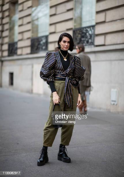 Brittany Xavier is seen wearing striped blouse khaki pants during Paris Fashion Week Womenswear Fall/Winter 2019/2020 on March 01 2019 in Paris France