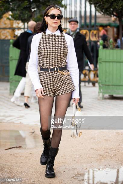 Brittany Xavier, wearing a pied de poule jumpsuit, white shirt, black boots and Dior bag, is seen outside Dior, during Paris Fashion Week -...