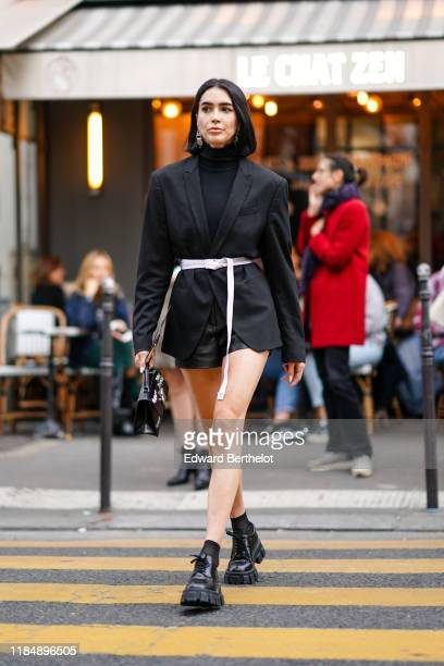 Brittany Xavier wears a black blazer jacket a white belt a black turtleneck top black shoes outside OffWhite during Paris Fashion Week Womenswear...