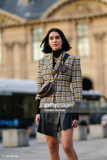 Brittany Xavier wears a checked pattern blazer jacket a brown Vuitton monogram logo bag a Vuitton mini bag attached to the shoulder strap golden...