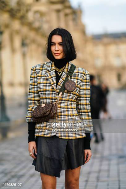 Brittany Xavier wears a checked pattern blazer jacket, a brown Vuitton monogram logo bag, a Vuitton mini bag attached to the shoulder strap, golden...