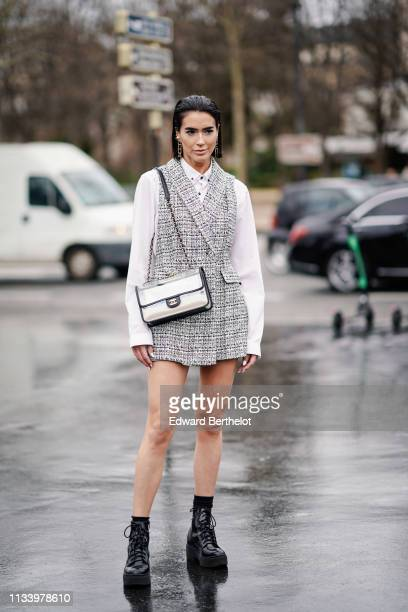Brittany Xavier wears a white shirt, a sleeveless tweed gray jacket, a Chanel bag, earrings, outside Chanel, during Paris Fashion Week Womenswear...