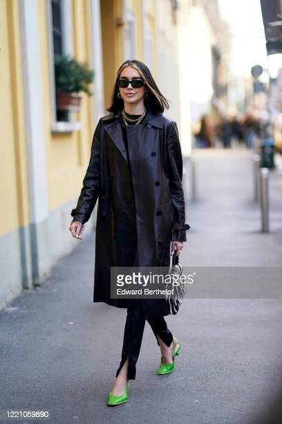 Brittany Xavier wears sunglasses, a black leather long coat, a golden necklace, a black and white zebra print bag, pants, green pointy shoes, outside...