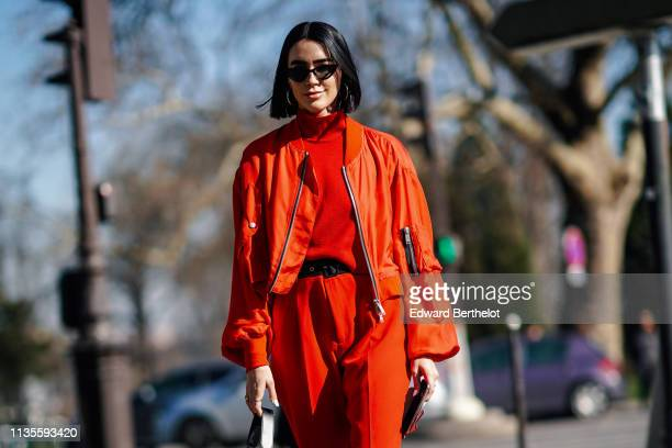 Brittany Xavier wears sunglasses a red turtleneck a black belt red pants an orange bomber jacket outside Unravel Project during Paris Fashion Week...
