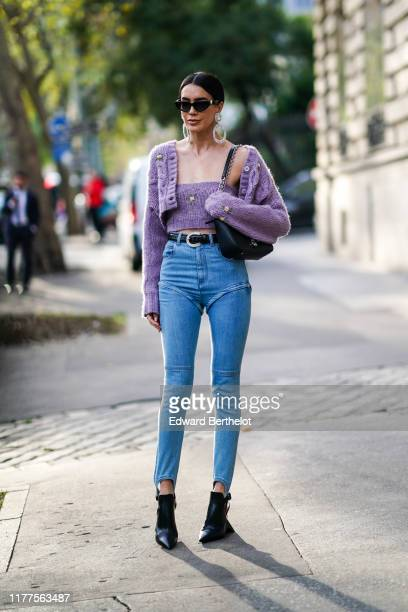 Brittany Xavier wears sunglasses glittering earrings a mauve knit strapless crop top a mauve knit crop jacket a black bag a black belt with a...