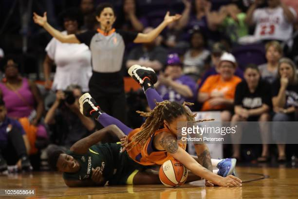 Brittney Griner of the Phoenix Mercury falls over Natasha Howard of the Seattle Storm as they attempt to control the ball during game three of the...
