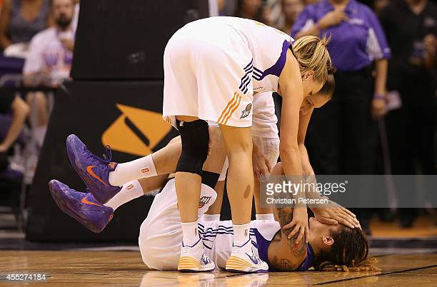 Brittney Griner of the Phoenix Mercury is looked at by Diana Taurasi and Penny Taylor after receiving a cut above her right eye during the first half...